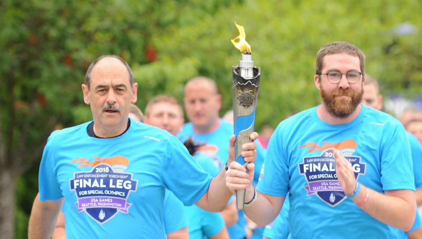 Captain Keller runs with Special Olympics torch, with other runners
